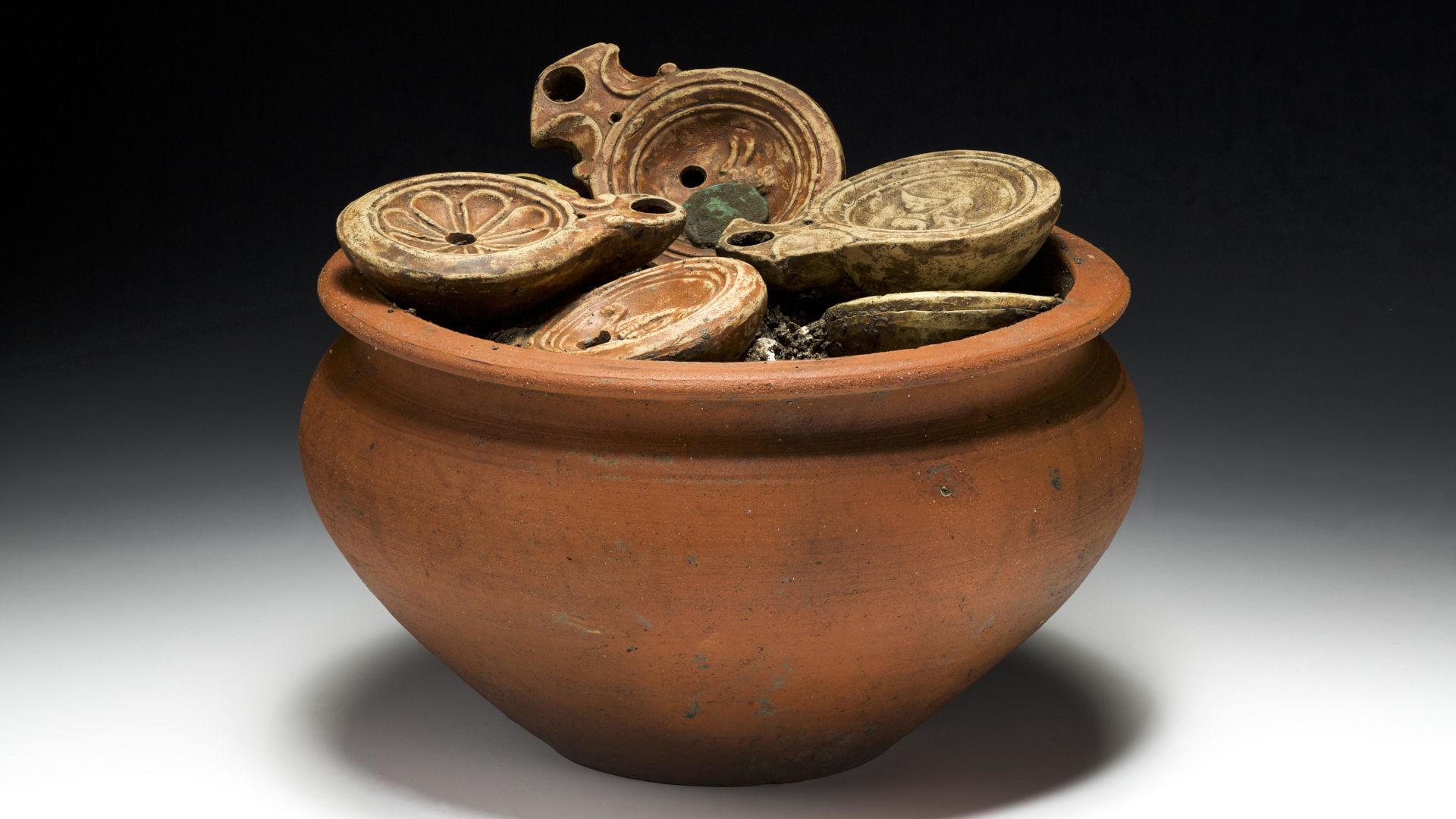 Ein römischer Kochtopf randvoll gefüllt mit Lampen und Münzen. Photo credits: © 2016 Kantonsarchäologie Aargau (Foto: Bela Polyvas).