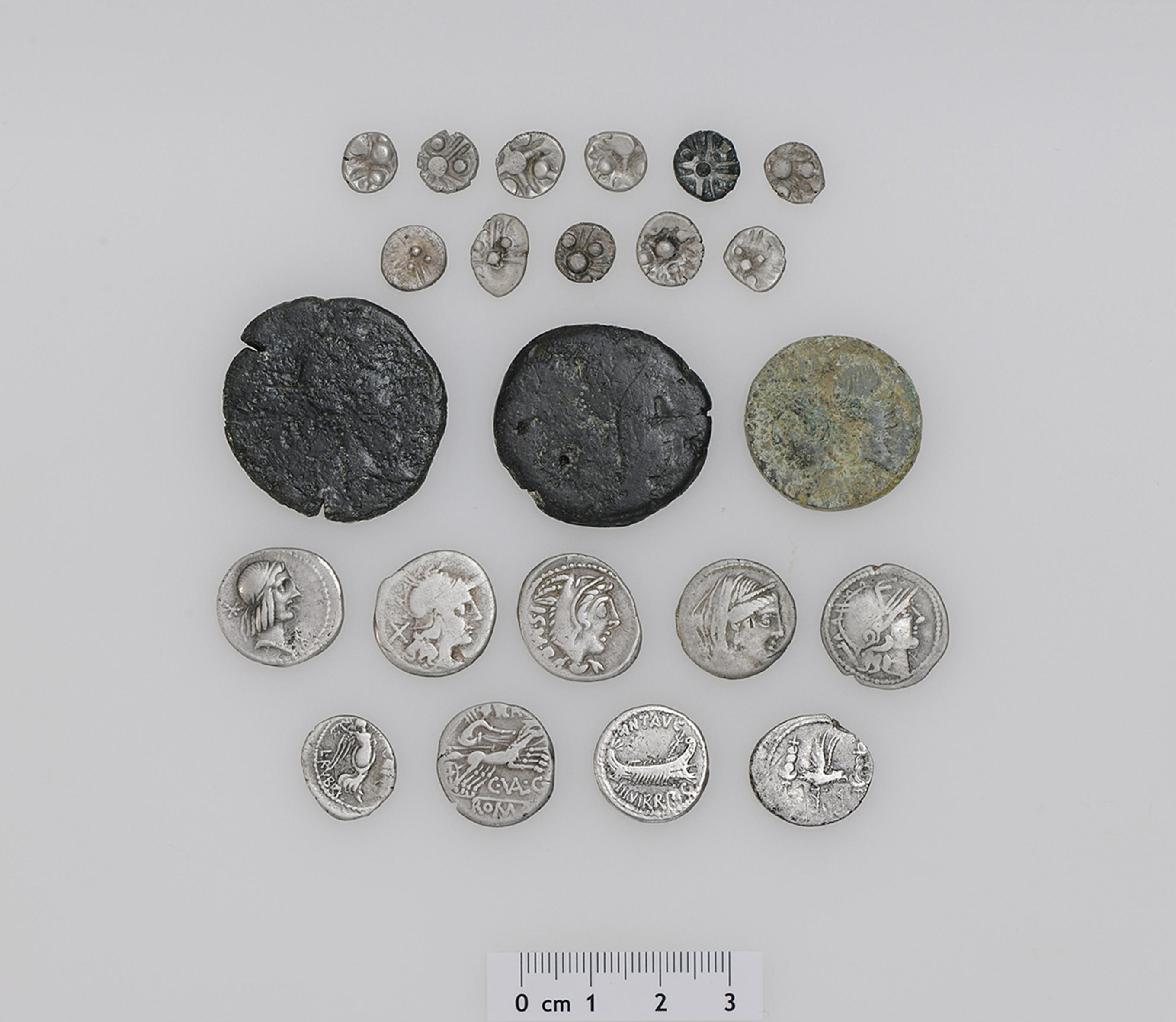 Die 23 Silber- und Bronzemünzen aus keltischer und römischer Zeit sind über 2000 Jahre alt. Es ist erst der zweite Mischfund von keltischen und römisch-republikanischen Silbermünzen in der Schweiz. Zu den 11 norischen Silbermünzen (Reihe 1 und 2 auf dem Foto) gibt es schweizweit keine Vergleichsfunde. Der Fund umfasst weiter 8 römische Silber- und 3 Bronzemünzen sowie die Imitation einer römischen Silbermünze, vermutlich aus dem südosteuropäischen Raum (Reihe 3 bis 5 auf dem Foto). Die römischen Silber-Denare und der Quinar (Reihe 4 und 5 auf dem Foto) weisen die Namen der Münzmeister C. Valerius Flaccus, L. Thorius Balbus, L. Piso Frugi und L. Rubrius Dossenus sowie den Namen des Feldherrn Marcus Antonius auf. Das jüngste Fundstück wurde um 15–9/7 v. Chr. in Nemausus, dem heutigen Nîmes (Frankreich), geprägt und gibt einen Hinweis darauf, ab wann der Schatzfund in den Boden gelangt ist. Foto: Res Eichenberger (Amt für Denkmalpflege und Archäologie des Kantons Zug).